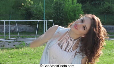 Sexy swag girl with red lips posing outdoors on football soccer play field. Young beautiful girl having fun on a sunny summer day. Cute happy female playing with hair in spring park. Backlit sunlight