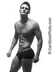 sexy tattoed fitness model wearing pants
