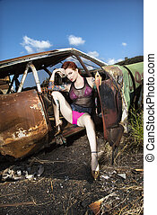 Sexy tattooed Caucasian woman sitting seductively in old rusted car in junkyard.
