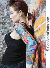 Sexy tattooed woman. - Sexy tattooed Caucasian woman leaning...