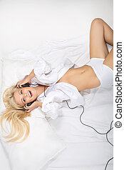 Sexy topless girl laying in bed with headphones
