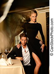 Sexy well-dressed young couple in luxury restaurant interior...