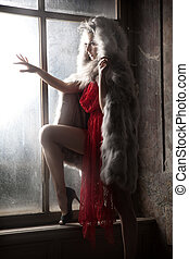 Sexy woman as a red hood looking out window