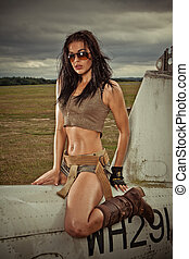 Sexy woman astride aircraft fuselage