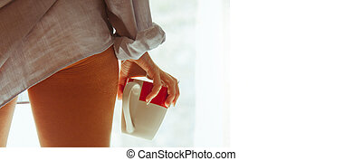 sexy woman at the window with cup of coffee