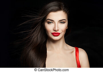 Sexy woman brunette with dark straight hair and red lips makeup. Happy girl on black background
