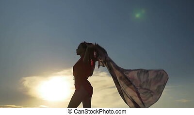 Sexy woman dancing and holding a scarf on the beach