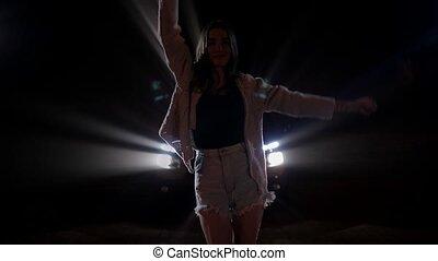 Sexy woman dancing in car headlights at night