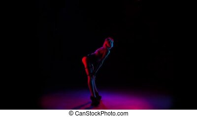 Sexy woman dancing in studio. Black background, slow motion