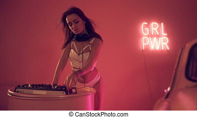 Sexy woman DJ playing on turntables in pink background