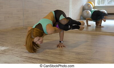 Sexy woman doing stretching exercises at the gym.