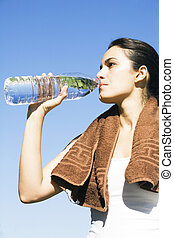 Sexy woman drinking water after exercise