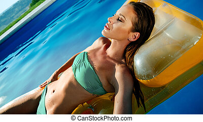 Sexy woman enjoying summer in pool