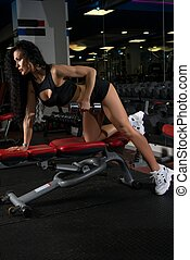 Sexy woman exercising on a simulator in gym