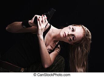 Sexy woman holding gun on dark