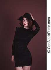 Sexy woman in a black dress and hat