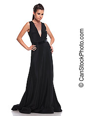 sexy woman in a black long dress is looking away