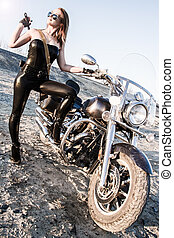 Sexy woman in a leather clothes near the bike