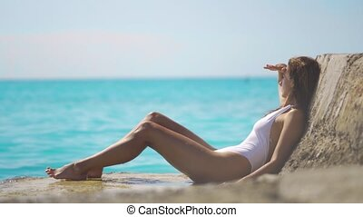 Sexy woman in a stylish swimsuit resting on the sea, looks out into the distance