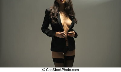 Beautiful and sexy young brunette woman in black lingerie and blazer dancing over gray studio wall background - video in slow motion