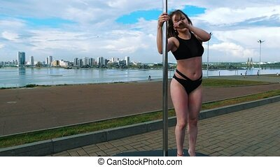 Sexy woman in black lingerie performs a pole-dance outdoors at summer day, close up