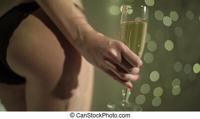 Sexy woman in black panties holding champagne glass over...