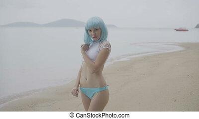 Sexy woman in blue wig and bikini.