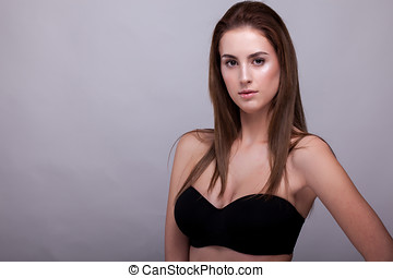 Sexy woman in bra with natural make up on gray background in...