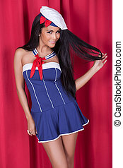Sexy gorgeous woman in cute nautical outfit with miniskirt and beret posing on a stage against red curtains