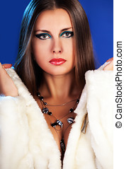 Sexy woman in fur with jewellery on blue winter background