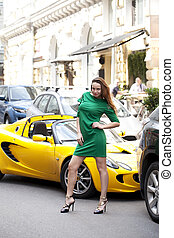 Sexy woman in green dress and super car