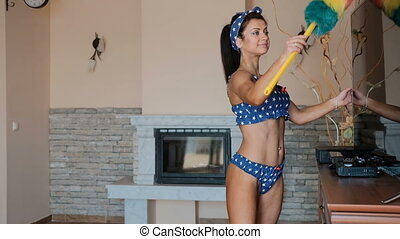 Sexy woman in her underwear wipes dust in room with a whisk.
