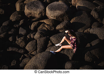 Sexy woman in jeans overall and pink t-shirt sit on big stone at rock beach sea ocean shore. Modern hipster girl have fun. Good sunny summer day
