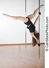 Sexy woman in pole fitness class