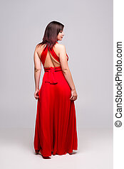Sexy woman in red dress in studio on gray background, full-length portrait