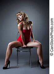 sexy woman in red dress sit on chair