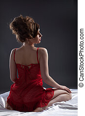 Sexy woman in red portrait on white silk bed