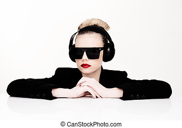 Sexy woman in sunglasses listening to music