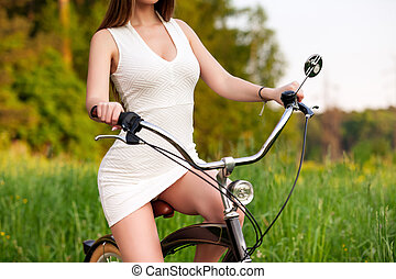 Sexy woman in white dress riding on a black bicycle
