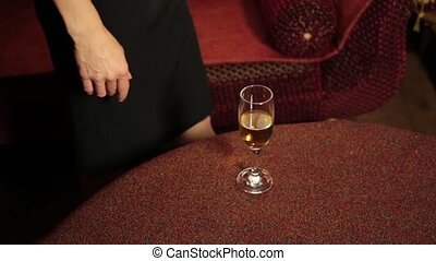 sexy woman legs in a black dress goes past the couch and puts a glass of champagne on a table