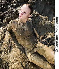Sexy woman lying in the mud and all stained