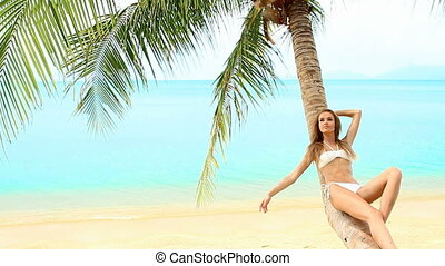 Sexy woman lying on palm tree at th