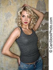 Sexy woman near grungy wall