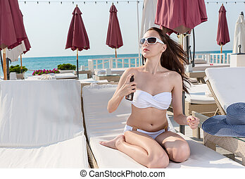 Sexy Woman on Lounge Chair Spraying Sunscreen
