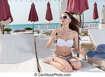Sexy Woman on Lounge Chair Spraying Sunscreen
