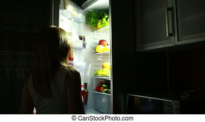 sexy Woman opens the refrigerator at night. selects a cucumber