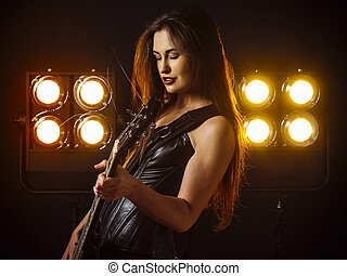Sexy woman playing electric guitar on stage