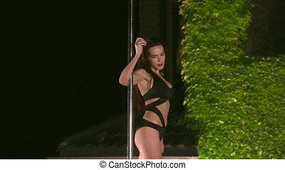 Sexy woman pole dancer in monokini performs pole dance poses