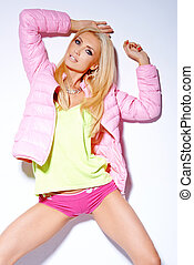 Sexy woman posing in pink jacket and shorts