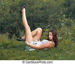 Sexy woman posing lying on grass outdoors